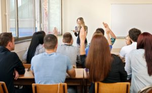 students in their classroom is raising her hand to giving answer