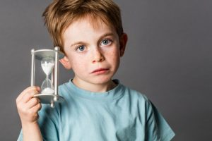 sad young boy with big blue eyes and freckles holding an egg timer, showing his anxiety for time concept, grey background