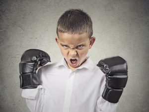 Closeup portrait headshot pissed off, Aggressive Child wearing Boxing Gloves, screaming, isolated on grey background. Negative human emotions, Face Expression, body language, life perception, attitude