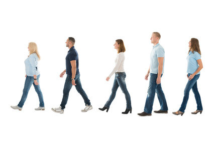 Full length side view of men and women walking in queue isolated on white background